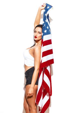julio: Mujer atractiva la celebración de EE.UU. bandera en la pared blanca, Fouth de julio