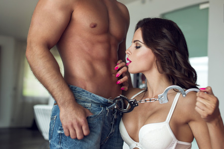 sexo pareja joven: Mujer atractiva que juega con los amantes machista cuerpo en el piso de lujo, las esposas y bdsm