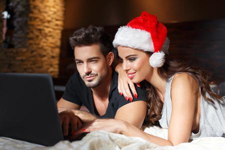 幸せな若いカップル クリスマス、赤いサンタ帽子でセクシーな女性のためのオンライン ショッピング
