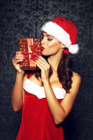 beso labios: Regalo de Navidad mujer morena sensual beso, labios rojos Foto de archivo