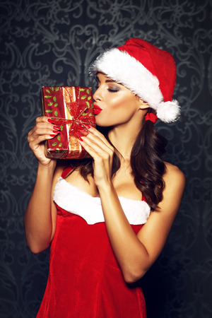 sexy santa: Sexy brunette woman kiss Christmas gift, red lips
