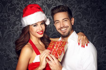 Young couple holding gift at Christmas, santa woman with boyfriend teeth smile
