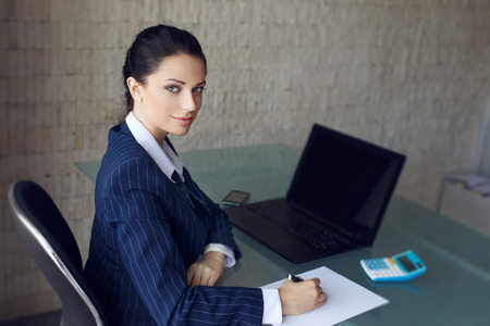 Accountant calculating taxes in office in formal wear, laptop, calculator and write on blank paper Stock Photo