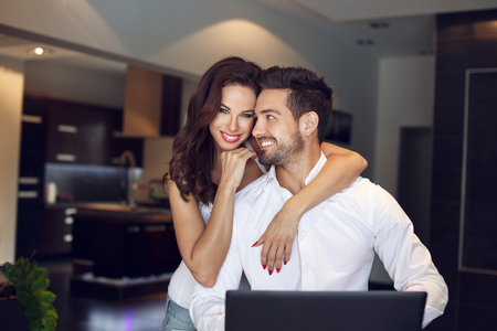 white smile: Happy young successful manager couple at home with laptop, confident people