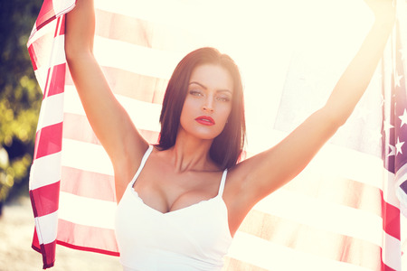 sexy brunette: Sexy woman holding USA flag outdoor, independence day, 4th of july