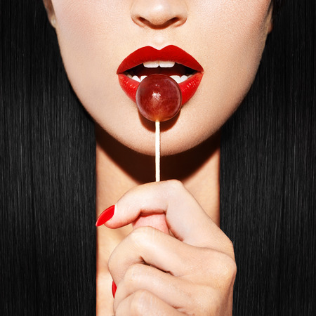 Sexy woman with red lips holding lollipop, beauty closeup Stockfoto