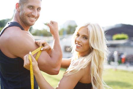 cinta metrica: Rubia mujer mans bíceps miden por cinta métrica amarilla en la naturaleza