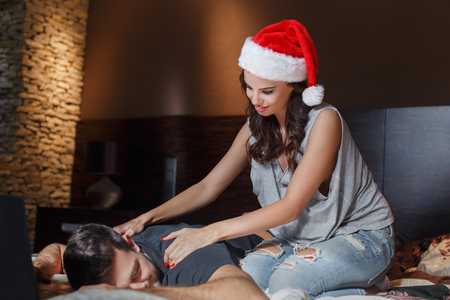 back rub: Young couple back rub on bed at home, santa woman massaging man