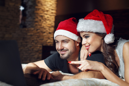 sexy couple in bed: Happy young couple searching for christmas gift online, love