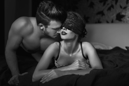 Sexy couple foreplay in bed black and white, bdsm