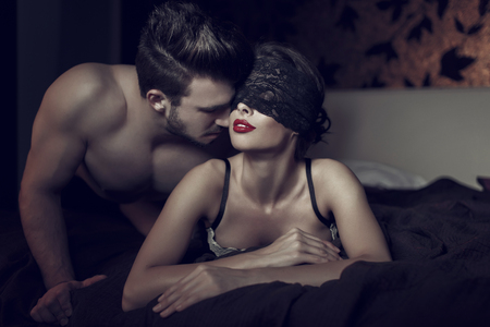 romance sex: Sexy woman in lace eye cover and red lips with young lover, foreplay in hotel room Stock Photo