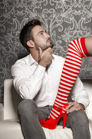 sex santa: Woman in sexy christmas outfit trying seduce man on sofa, foreplay