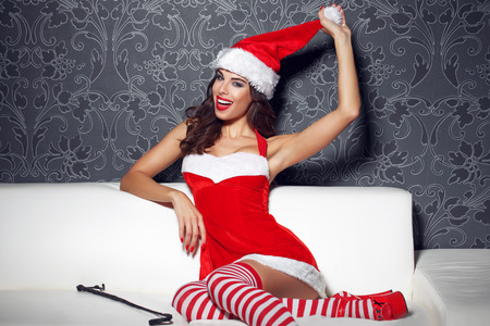sex girl: Sexy santa woman with whip pulling hat on sofa