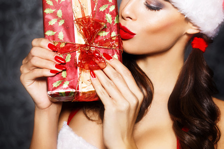 Sexy santa woman kissing gift closeup, red lips