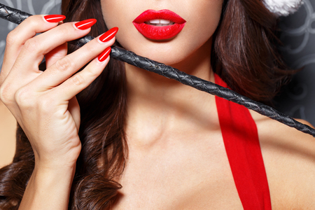 hot sex: Sexy brunette santa woman with whip closeup, bdsm