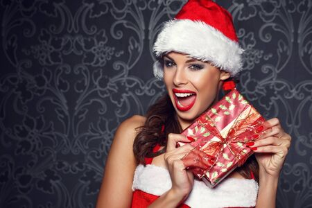 beautiful background: Sexy santa woman surprise with gift at vintage wall