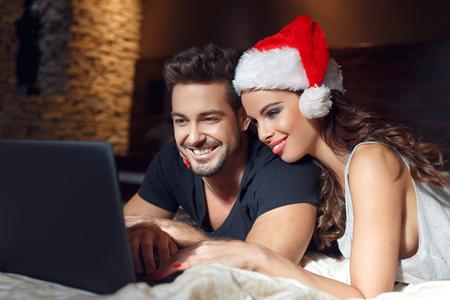 chicas de compras: Pareja joven en busca de regalos de Navidad en línea, acostado en la cama