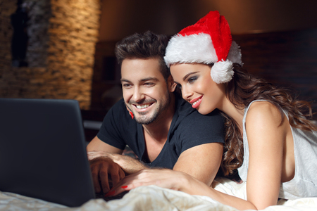 searching for: Young couple searching for christmas presents online, lying on bed Stock Photo