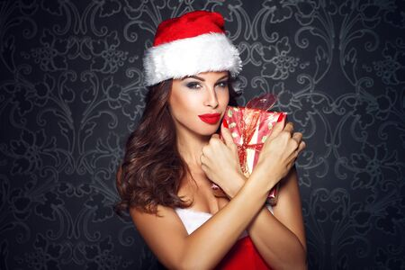 woman surprise: Sexy santa woman embrace christmas gift at vintage wall