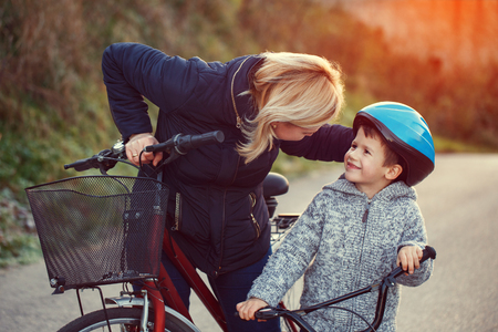 road cycling: Mother teaching son cycling at outdoor in sunset Stock Photo