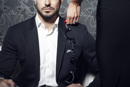 セクシーな女性の緊縛、夜にソファーに裕福な実業家を誘惑しようとしています。 写真素材