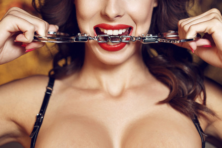 seks: Sexy vrouw bijten handboeien, rode lippen, bdsm Stockfoto