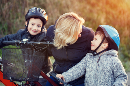 teaching children: Mother teaching cycling kids outdoor at fall Stock Photo