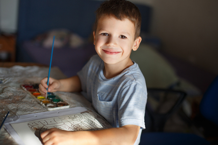 boy book: Little boy painting at home by watercolor coloring book Stock Photo