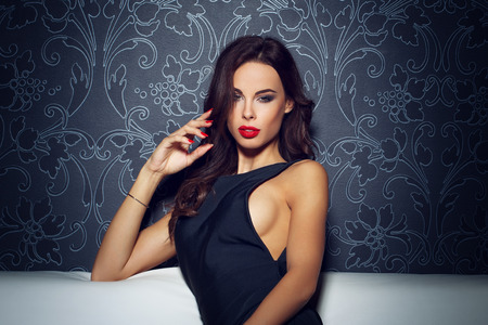 sensual sex: Sexy sensual woman sitting on sofa, red lips, seduction Stock Photo