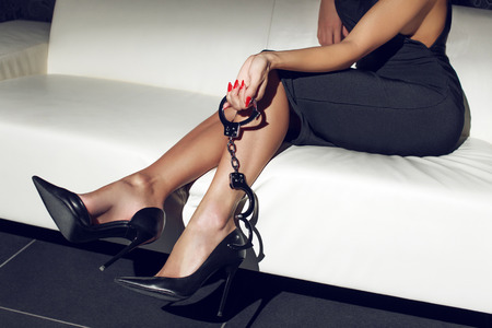 nude woman sitting: Sexy woman holding handcuffs on sofa, bdsm
