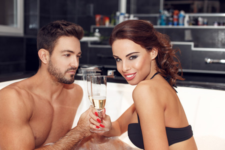 sexy young girl: Young couple drinking champagne in jacuzzi, enjoying bath Stock Photo