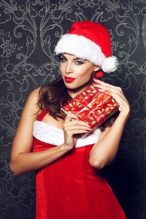 femme brune sexy: Sexy femme tenant de Santa bo�te de cadeau de No�l � vendange mur Banque d'images