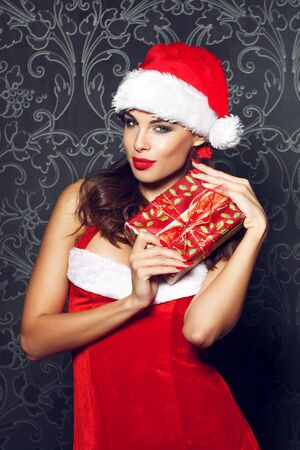 sexy brunette woman: Sexy santa woman holding christmas gift box at vintage wall