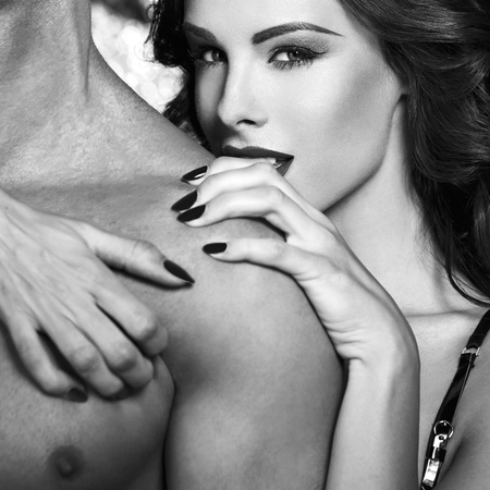 Sexy woman embrace naked man shoulder, black and white, bdsm