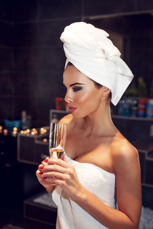 woman in bath: Woman with towel holding glass of champagne in bathroom