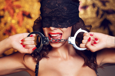Sexy woman bite handcuffs in lace eye cover, red lips and nails
