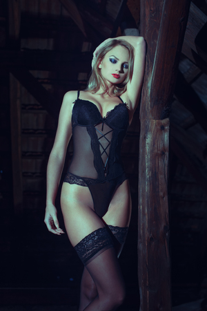 sensuality: Sexy blonde woman in black underwear posing in barn at night, closed eyes, sensuality
