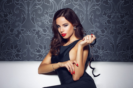 sex toys: Sexy sensual woman with red lips holding handcuffs, sit on sofa at vintage wall at night, red lips and nails, bdsm Stock Photo