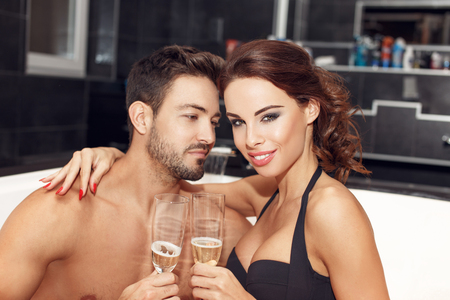 woman bathing: Happy young couple drink champagne in jacuzzi, honeymoon