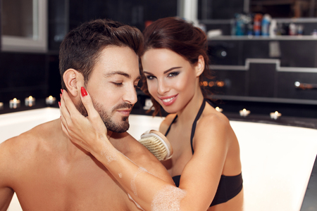 wife of bath: Happy young couple with brush in jacuzzi. woman washing mans back, using brush. Honeymoon Stock Photo