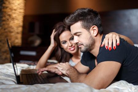 couple bed: Jeune couple achats en ligne sur le lit par ordinateur portable, femme étreinte homme épaule