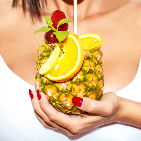 Woman hand holding pineapple tropical cocktail closeup. Drinking by straw, red nails.