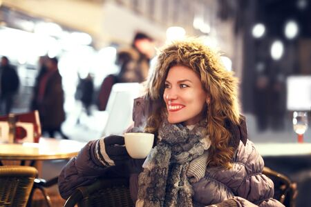 Woman drinking hot coffee outdoor at winter, teeth smile Stock Photo
