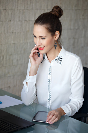 confide: Modern businesswoman typing on laptop, red lips, in office