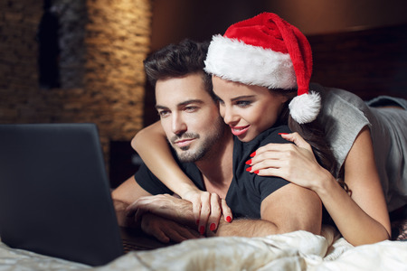 Happy young couple searching for christmas gift online, love