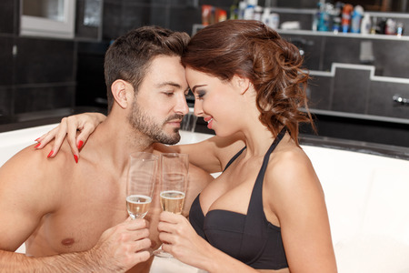 wife of bath: Happy young couple drink champagne in jacuzzi, honeymoon