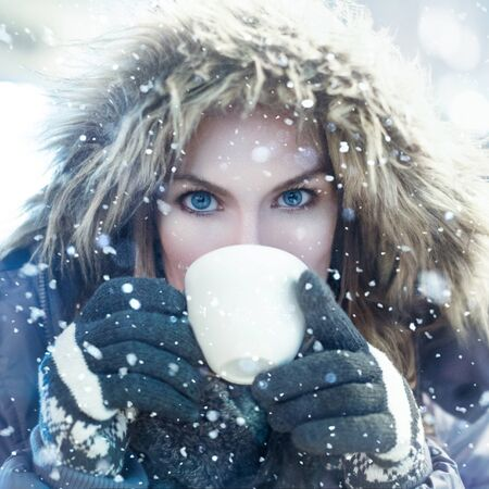 female hands: Winter woman drink from white mug in snowfall