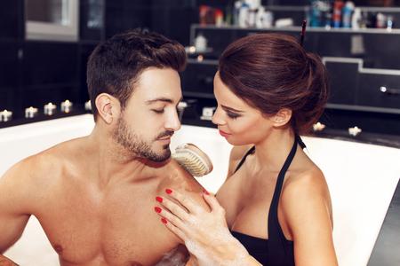 salud sexual: Lava de la mujer al hombre de vuelta con brocha en el jacuzzi, pareja sensual durante la luna de miel Foto de archivo
