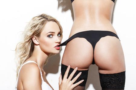 ragazza nuda: Sexy bionda donna morso amanti mutandine, i preliminari lesbica a muro bianco Archivio Fotografico