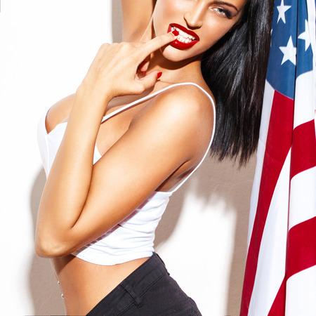 julio: Mujer atractiva con los labios rojos que sostienen la bandera de EE.UU. en la pared blanca